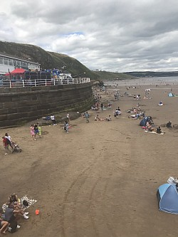 Whitby beech with crowds gathering.